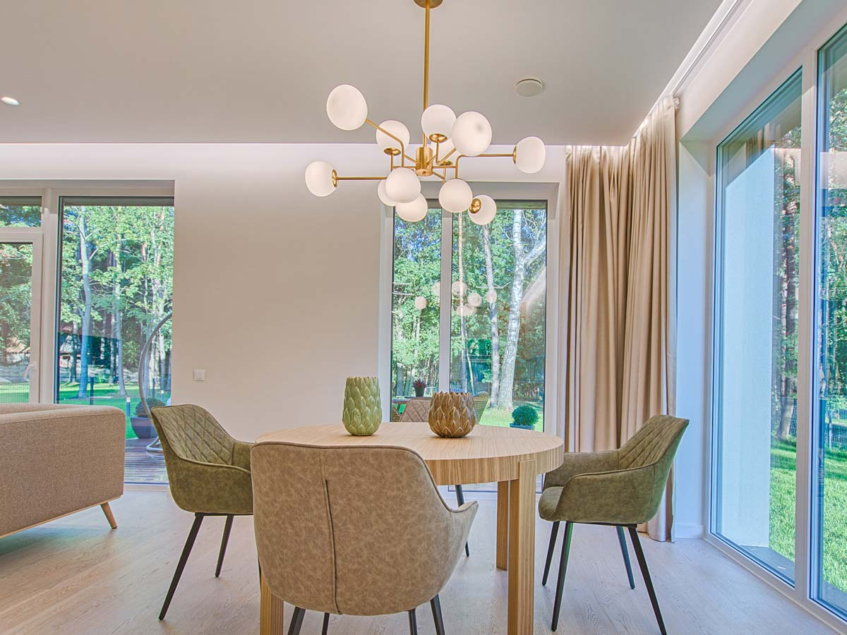 dining area of table and four chairs under large hanging chandelier