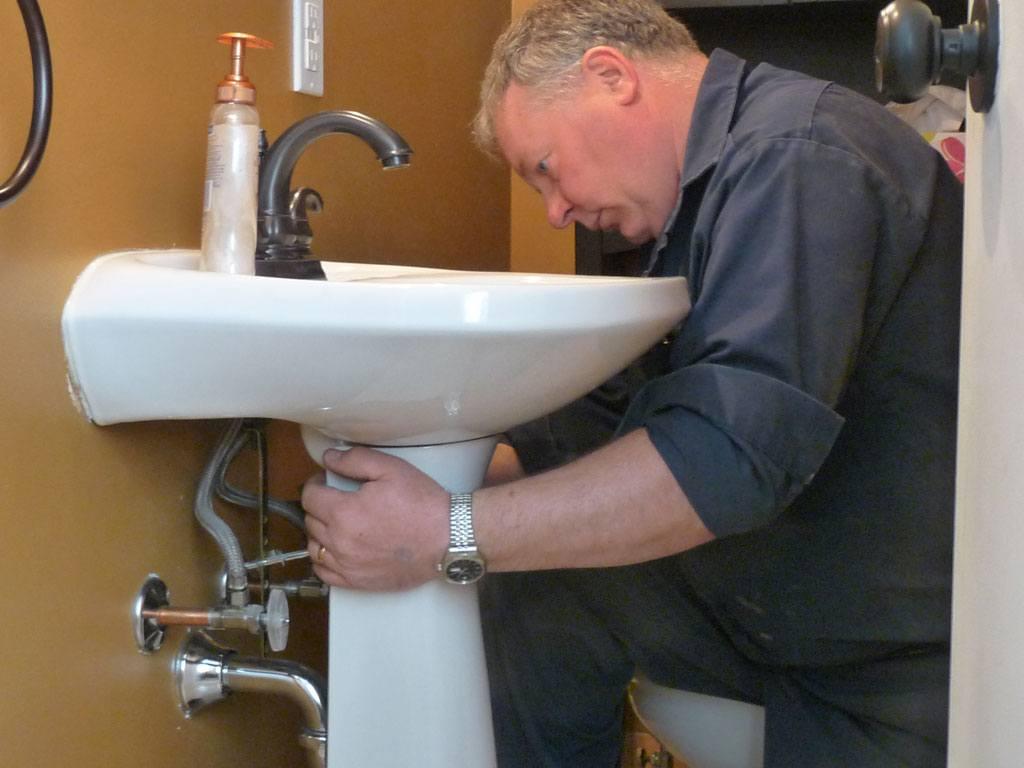 plumber working on bathroom sink installation